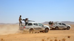 FILE PHOTO. Syrian soldiers ride atop armed pick-up trucks. EPA, STR