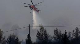 ΦΩΤΟΓΡΑΦΙΑ ΑΡΧΕΙΟΥ. Ελικόπτερο ρίχνει νερό προσπαθώντας να κατασβέσει πυρκαγιά σε δασική περιοχή. ΑΠΕ-ΜΠΕ, ΟΡΕΣΤΗΣ ΠΑΝΑΓΙΩΤΟΥ