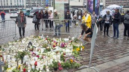 People place candles and flowers on a site of a stabbing at the Market Square in Turku, Finland, 19 August 2017. EPA/MARKKU OJALA