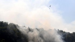 A helicopter flies over a burnt area of a forest fire in Dajti Mountain in Tirana, Albania. The Albanian Army assists to extinguish the fire as forest fires have spread all over Albania. EPA/MALTON DIBRA