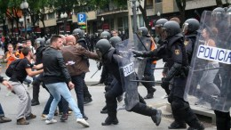 FILE PHOTO. Officers of National Police clash with people outside a polling center. EPA JAUME SELLART
