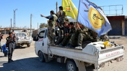 FILE PHOTO. Fighters from the Syrian Democratic Forces (SDF) pass by on a car at the Al-Na'im roundabout in central Al-Raqqa, Syria. EPA/YOUSSEF RABIH YOUSSEF