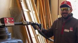 πάλληλος της ΕΚΟ γεμίζει με πετρέλαιο τη δεξαμενή του Δημοτικού Σχολείου Έμπωνα.