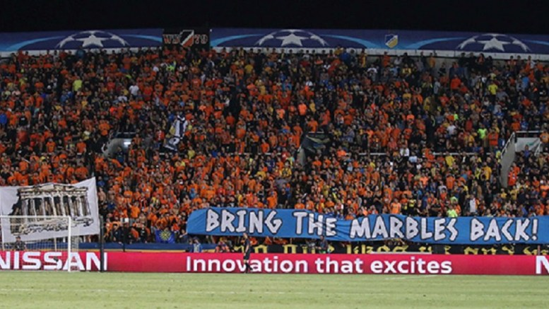 """«Η ιστορία δεν μπορεί να κλαπεί», «Φέρτε πίσω τα μάρμαρα», ήταν το μήνυμα στα πανό που σήκωσαν οι φίλοι των """"πορτοκαλί""""! στο αγώνα με την Τότεναμ στην Λευκωσία!! Φωτογραφία από την ιστοσελίδα του ΑΠΟΕΛ"""