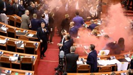 Members of Opposition in Albanian Parliament stand as smoke bombs are detonated during a vote for a new temporary general prosecutor in Tirana, Albania, 18 December 2017. Albanian police have clashed with opposition supporters outside the building trying to force their way into the Parliament. EPA, STR