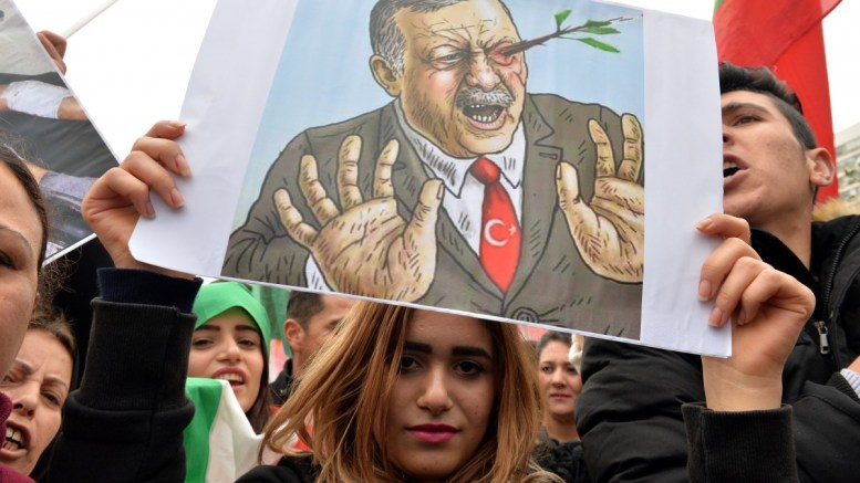 File Photo: A Kurdish protester carries a placard showing Turkish President Recep Tayyip Erdogan and olive branches during a protest against what they call the 'Turkish aggression' in northern Syria, in front of the European Union building in Beirut, Lebanon. EPA, WAEL HAMZEH