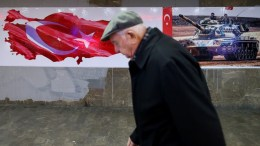 An elderly man walks in front of a wall covered with pictures of Turkish Army tanks and patriotic decoration in support of the Turkish military operation, Istanbul, Turkey. EPA, ERDEM SAHIN