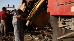 People inspect the deformed train coach after a passenger train collided with a freight train in the village of Kom Hamada in the northern province of Beheira. EPA, STR
