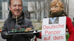 Demonstrators wearing masks to look like German Chancellor Angela Merkel (L) and Turkish President Recep Tayyip Erdogan hold banners saying 'No German weapons for islamist Erdogan' as they protest against the arms deals between Germany and Turkey and the current campaign in northern Syria (Afrin), in Berlin, Germany. EPA, OMER MESSINGER