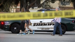 A group of persons walk in front of a Broward County sheriff car after a shooting at Marjory Stoneman Douglas High School in Parkland, Florida, USA, 14 February 2018. EPA, CRISTOBAL HERRERA