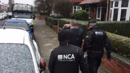 FILE PHOTO.  A handout photo)showing Officers from the NCA accompanying a man (C) at an unidentified address in Britain. EPA, NCA, HANDOUT HANDOUT EDITORIAL USE ONLY, NO SALES