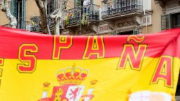 A man looks from his balcony as participants hold a Spanish national flag during a march towards the Memorial of soberanism icon Rafael Casanova called by Tabarnia Platform, an initiative for breakaway Catalonia region Tabarnia that promotes the debate against Catalan pro-independence process, in Barcelona, northeastern Spain, 04 March 2018. EPA, MARTA PEREZ