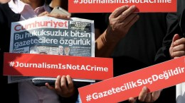 File Photo: People hold banners and copies of the current Cumhuriyet newspaper's edition and picture of arrested journalist Ahmet Sik in front of the Istanbul Courthouse before a trial against staff of Cumhuriyet newspaper in Istanbul  EPA, ERDEM SAHIN