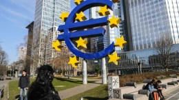 File Photo: A man wearing a monkey costume passes next to the 'Euro' sculpture in front of the old European Central Bank (ECB) building in Frankfurt. EPA, ARMANDO BABANI