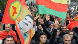 File Photo: Kurdish protesters flash the V-sign as they carry national flags and a picture of (PKK) leader Abdullah Ocalan. EPA, WAEL HAMZEH