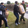 Glenn and student volunteers carry compost at a 2015 event.