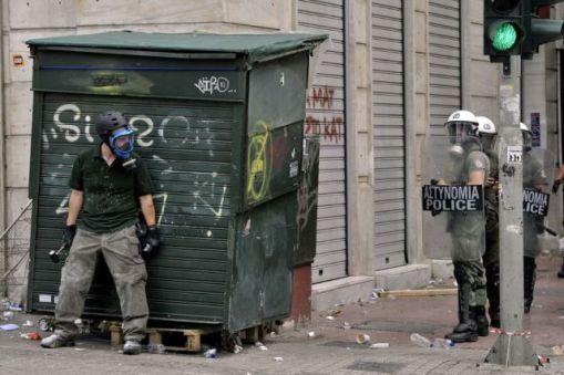 homem escondido atras de uma lixeira indoa taar policia de choque