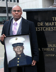 Kenneth Chamberlain jr holding a picture of his father