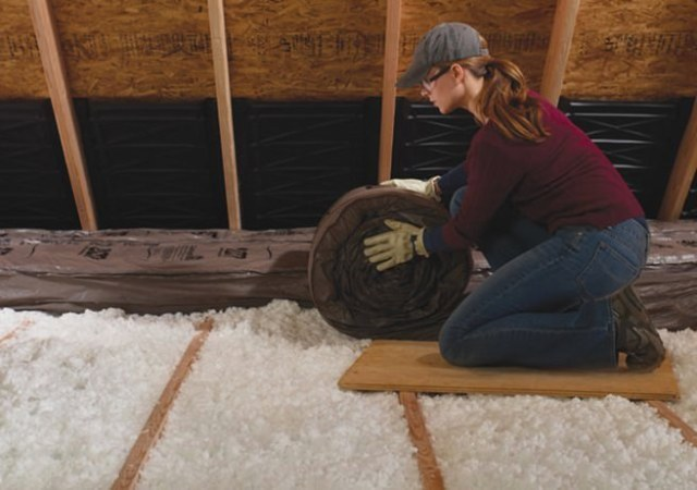 Woman laying insulation in a loft space