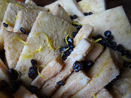 bread sprinkled with custard mix, currants and lemon zest