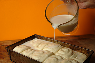 Pouring sweetened coconut milk on the risen panipopo dough | H is for Home