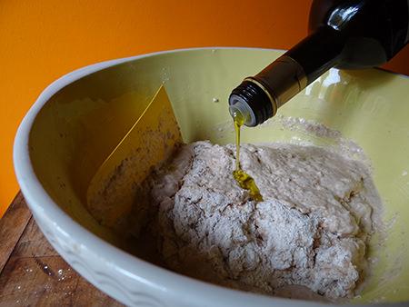 Adding olive oil to Roman bread dough