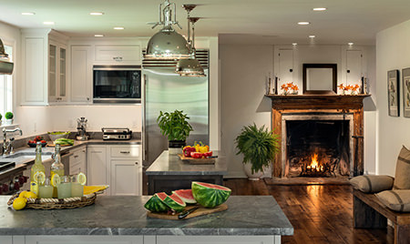 Open fireplace with wood mantelpiece in a kitchen-lounge