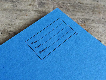 vintage blue covered exercise book showing name, form and subject label