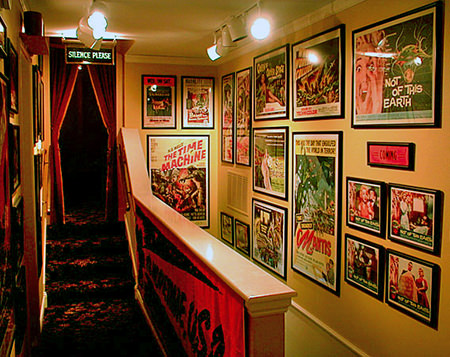 vintage film posters on a wall going up stairs to a home cinema