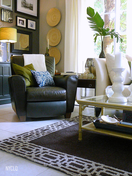 corner of a sitting room with army green leather club chair