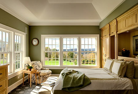 Army green painted double aspect bedroom