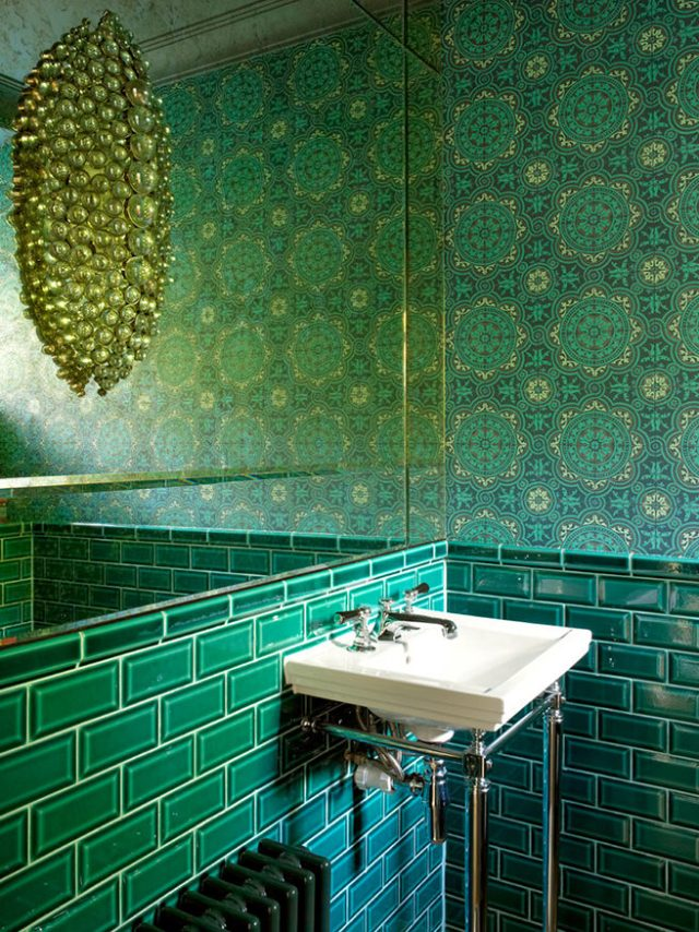 Cloakroom with emerald subway tiles and patterned wallpaper