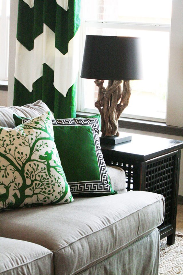 Emerald & white patterned cushions and curtain in a sitting room