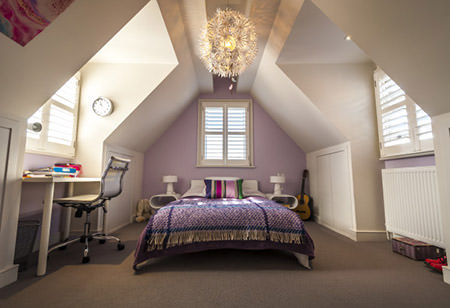 attic bedroom with mauve painted feature wall