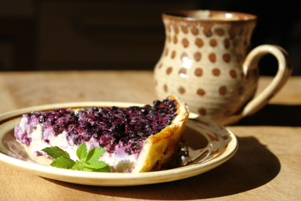 plate with a slice of bilberry tart and cup of tea