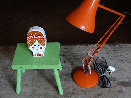 Green-painted wooden antique milking stool, Carltonware Princess money box and orange Anglepoise lamp