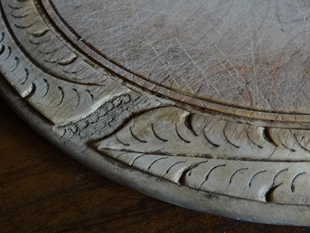 Detail from an antique carved wooden bread board