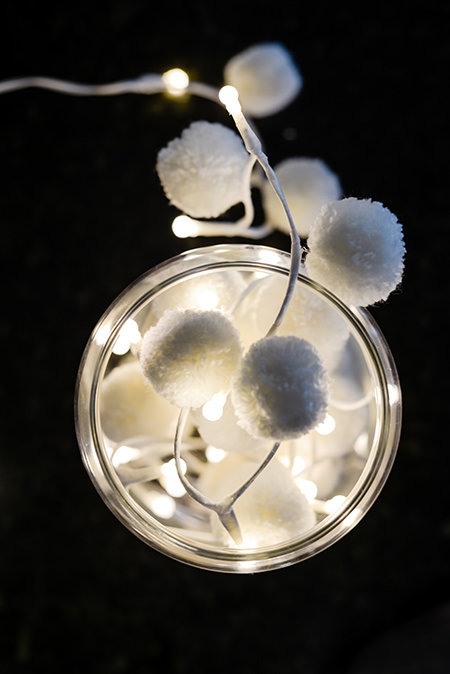 Lit white PomPom Galore fairy lights on a black background