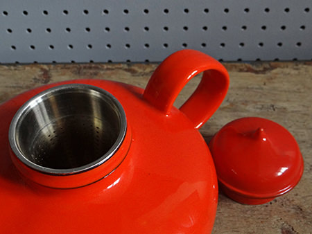 orange Rörstrand Pop teapot with lid off showing the strainer