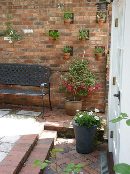 herbs growing in small terra cotta pots on a red brick wall