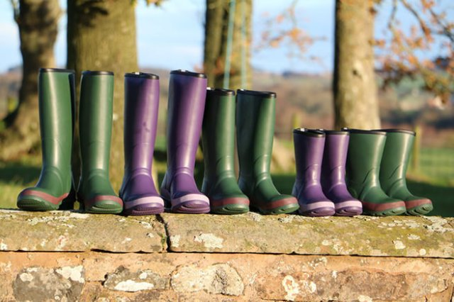 Line up of Warm Welly Co. wellies on a wall in the countryside