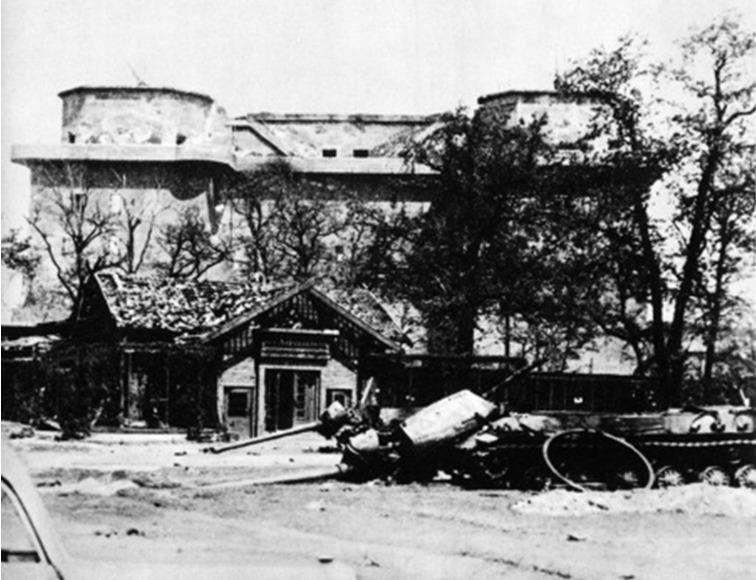 Op de voorgrond: achtergelaten beschadigd oorlogsmaterieel in de zoo na de Slag om Berlijn. Het gebouw op de achtergrond is de zogenoemde Zoo-Flakbunker, een gigantische betonnen schuilbunker voor burgers met bovenop luchtafweergeschut. (Publiek Domein / Wikimedia Commons)