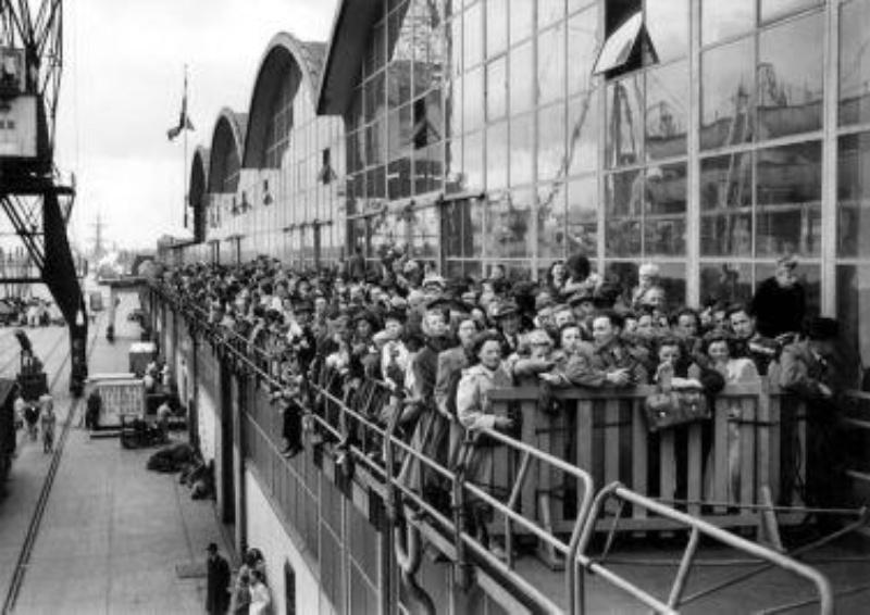 """Emigranten naar Canada wachten in Rotterdam tot zij aan boord kunnen van de S.S. """"Volendam"""". Nederland, Rotterdam, 15 mei 1951"""