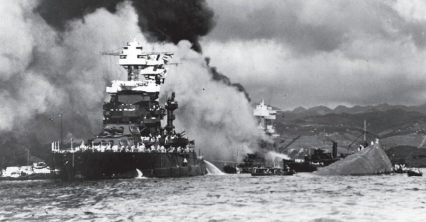 De aanval op Pearl Harbor, 7december 1941. De uss Maryland naast de gekapseisde uss Oklahoma; de uss West Virginia staat in brand.  ©Naval Historical Foundation, Washington DC