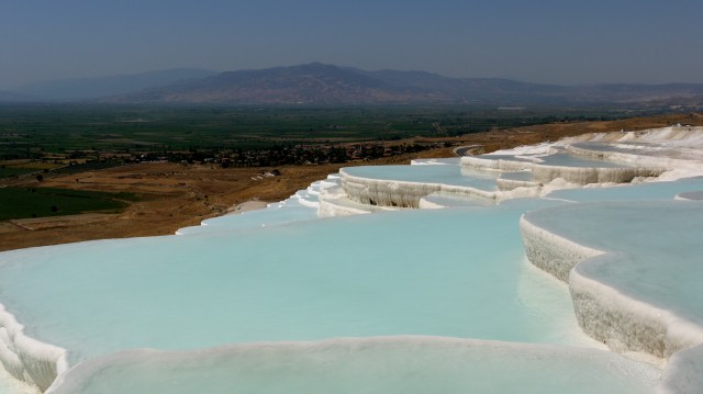 Beautiful, crystal clear water pools with plains in the background - Pamukkale, Turkey