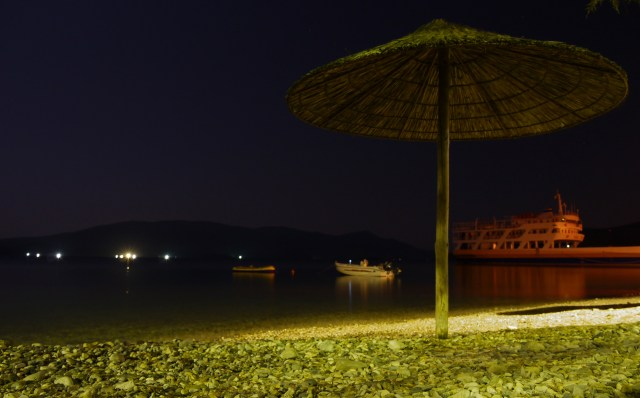 The silent port and beach parasol at night - Glyfa, Greece