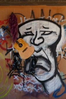 "Artistic ""collage"" of graffiti, an old guitar and leather boots. Seen in Bombay Beach"