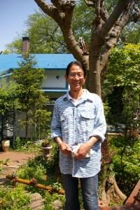「日吉山荘」と鼠入俊之さん。日吉のマンション住まいの頃から「植木鉢がだんだんベランダに増えてきていました」と、この家を購入前からも花や草木に癒されていたと教えてくれました
