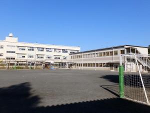 グラウンドに2階建てのプレハブ校舎が建てられている大曽根小学校