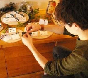フロラシオンのディスプレイをアレンジするエスネスさん。アクセサリーの素材は木やウォルナット、アクリルなど。東京の工房で作成している